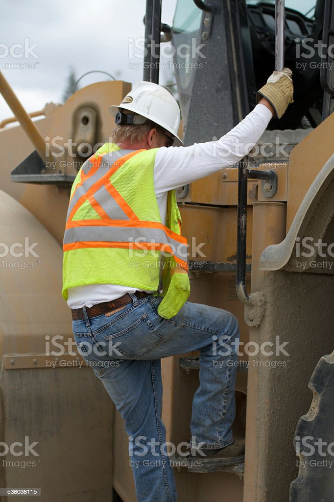 Construction worker climbing stairs Safely on machinery stock photo