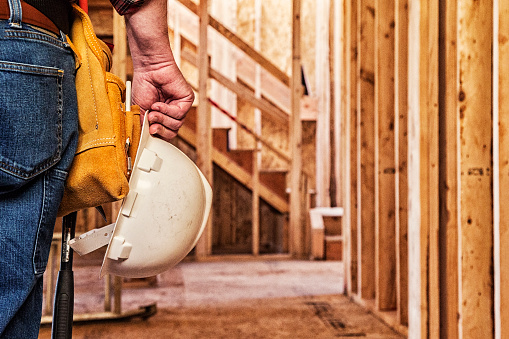 Photo of a construction worker with a white hard hat in one hand, closeup crop.