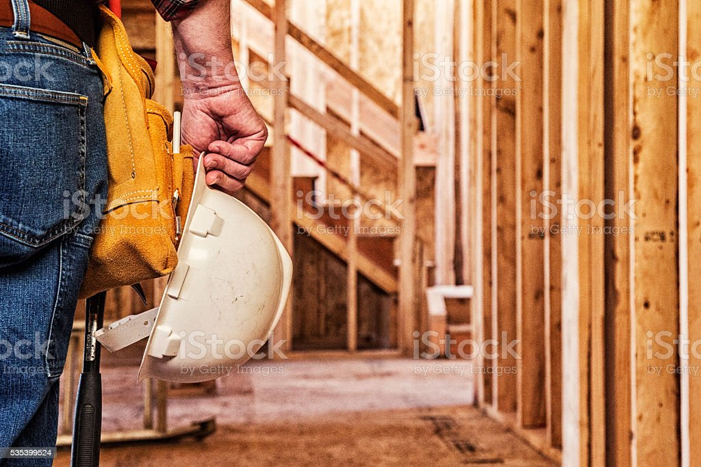 Construction Worker Closeup with Hardhat in Hand stock photo