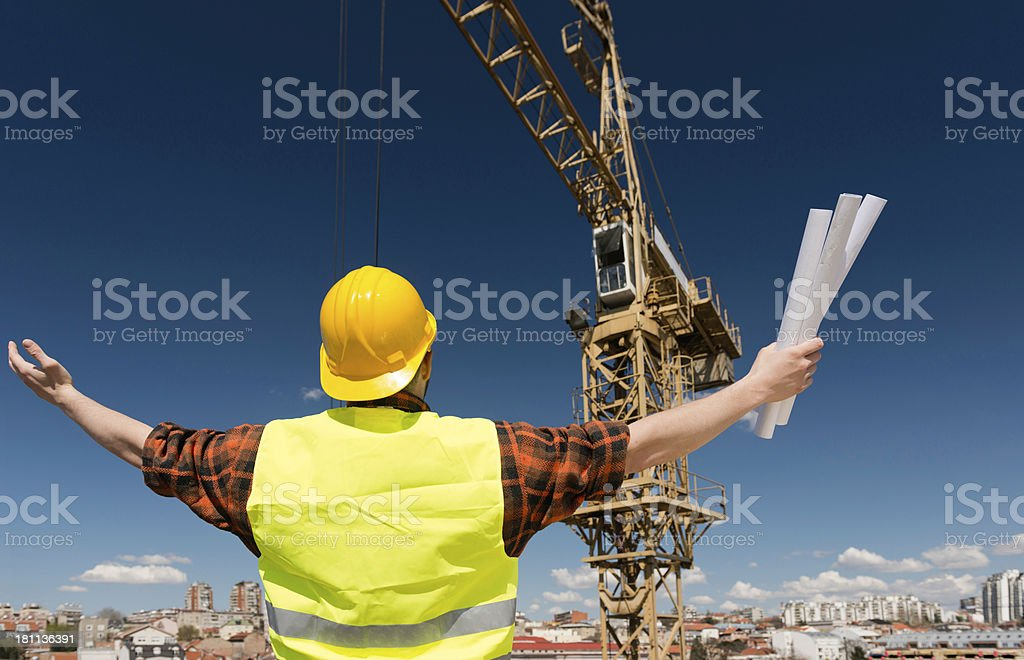 Construction worker communicating with crane operator stock photo