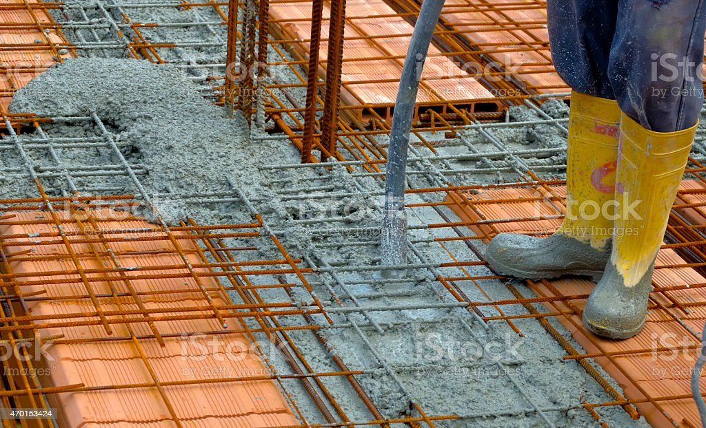 Construction worker compacting liquid cement stock photo