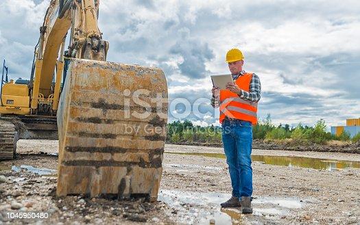 Construction worker Earth Digger Driver checking blueprint on digital tablet