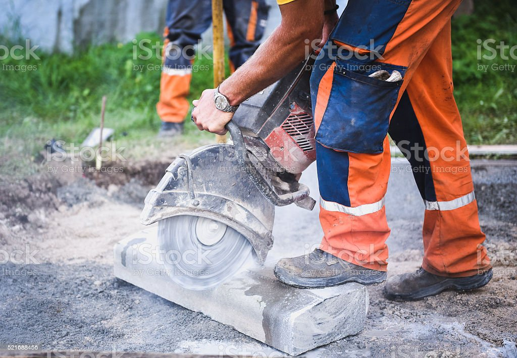 Construction worker cutting concrete paving stabs or metal for s stock photo