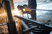 Construction worker cutting steel rods in construction factory using grinder.
