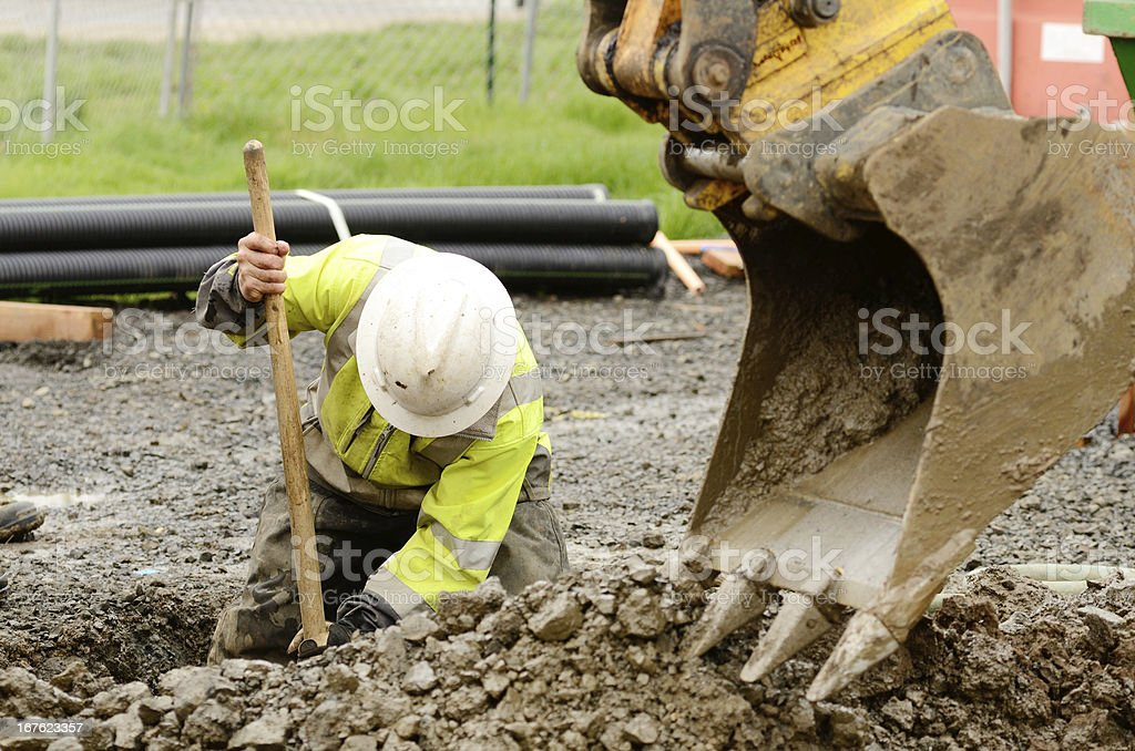 Construction worker digging dirt out with the help of crane stock photo