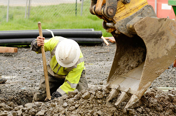 construction worker digging dirt out with the help of crane - greppel stockfoto's en -beelden