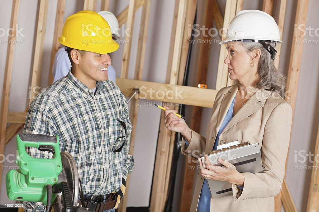 Construction worker discussing plans with builder royalty-free stock photo