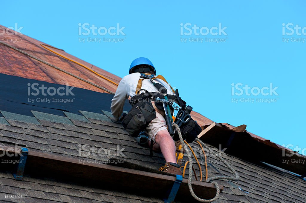 Construction worker doing work on a rooftop royalty-free stock photo