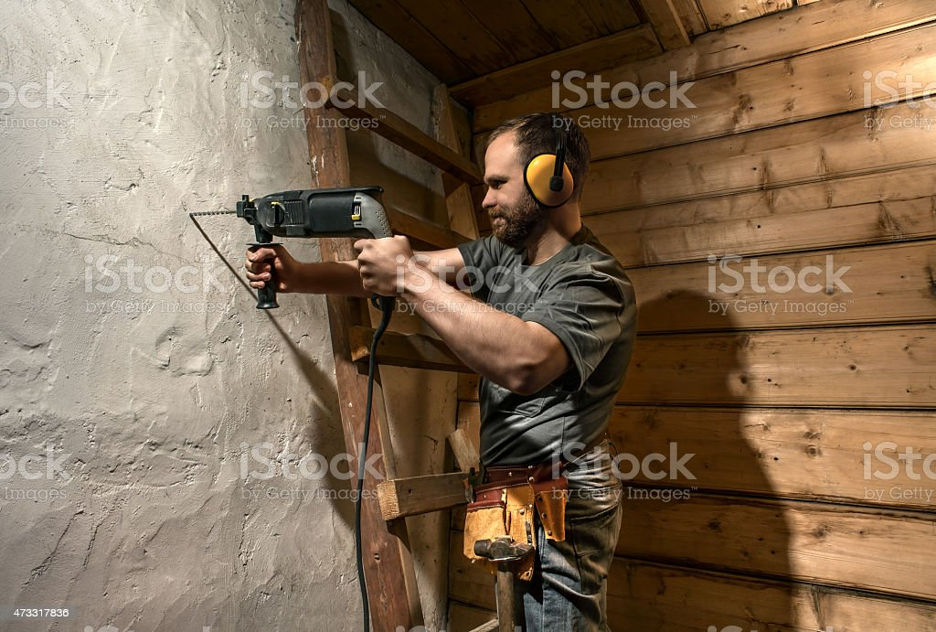 construction worker drill perforate concrete wall stock photo
