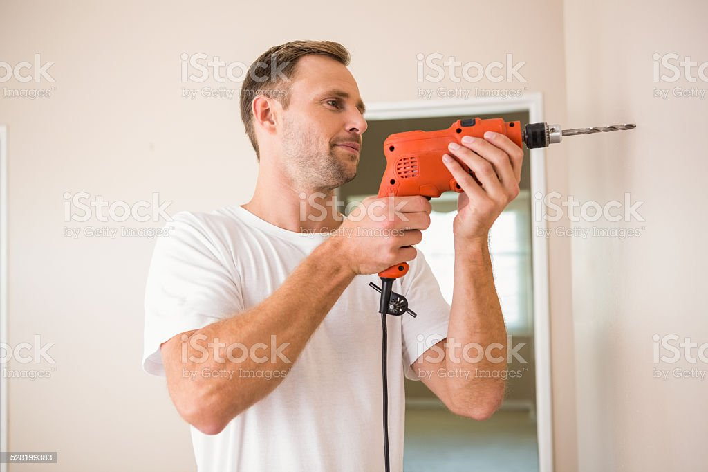 Construction worker drilling hole in wall stock photo