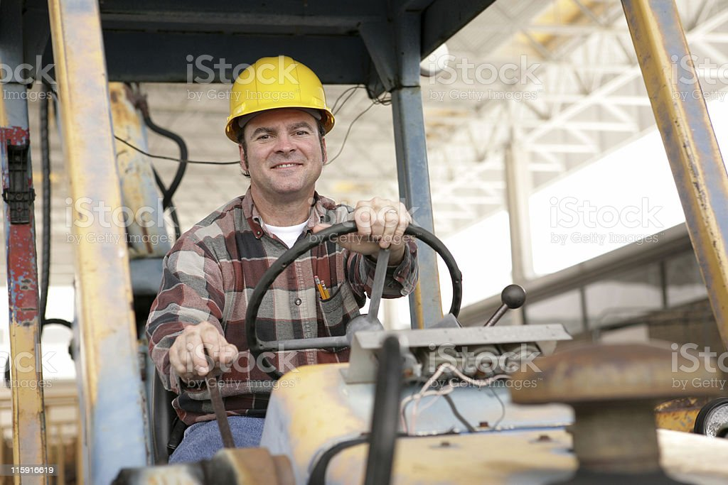 A construction worker driving a machine stock photo