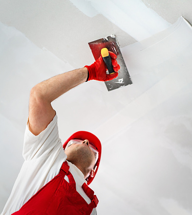 Closeup low angle view of a mid 40's man using a trowel for flattening a layer of gypsum over a ceiling and making it as flat as possible before painting.