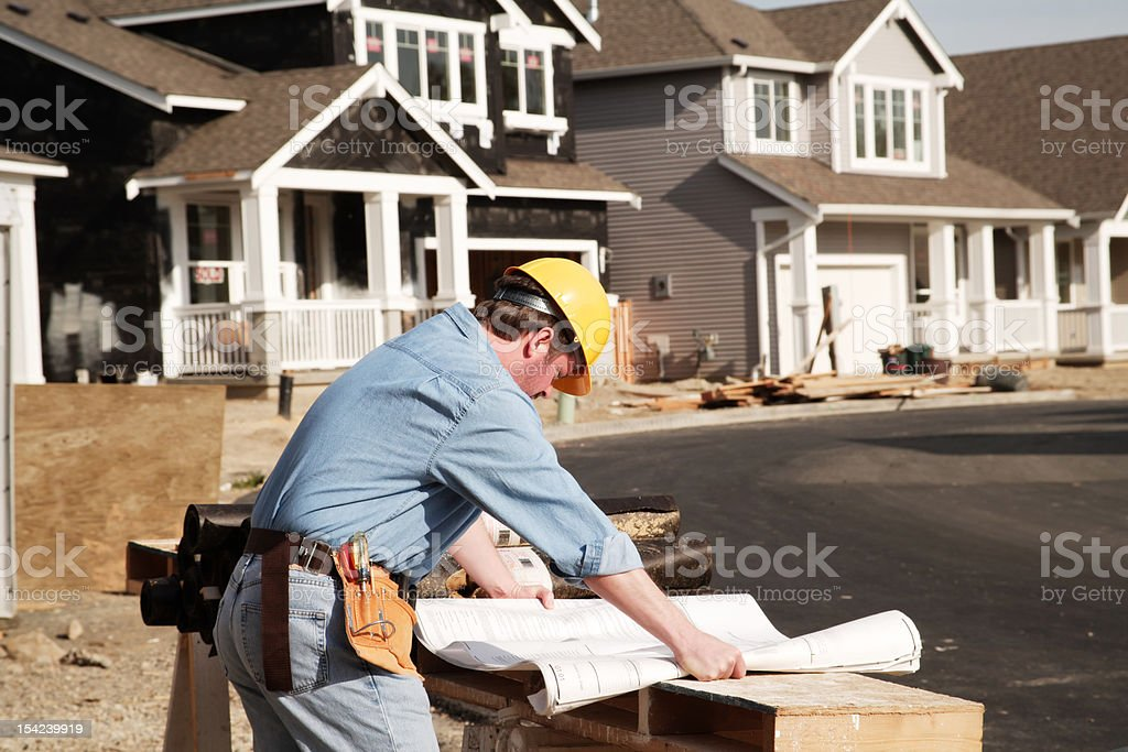 Construction worker examined building plans blueprints stock photo