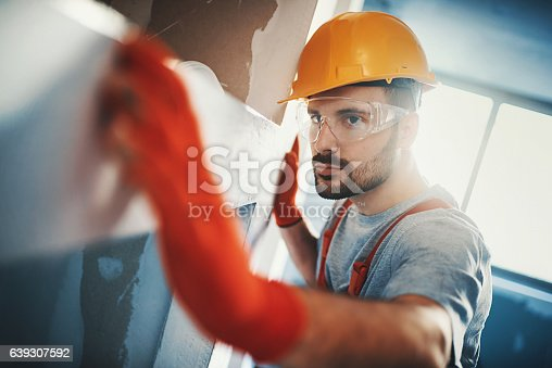 istock Construction worker examining a drywall. 639307592