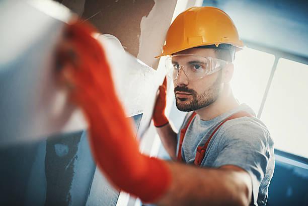 Construction worker examining a drywall. - foto de acervo