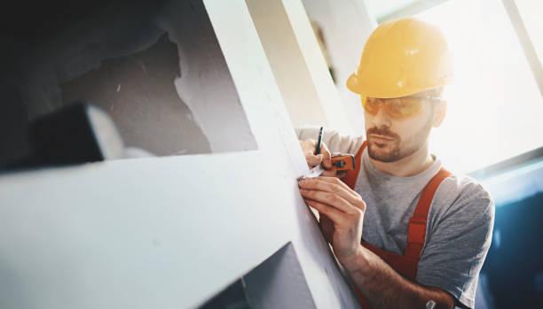 Trabalhador da construção civil examinando do drywall. - foto de acervo