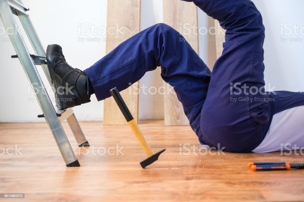 Construction worker falling down the ladder stock photo