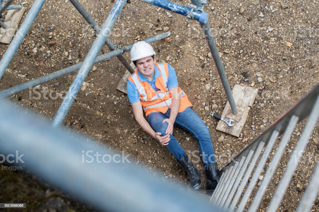Construction Worker Falling Off Ladder And Injuring Leg stock photo