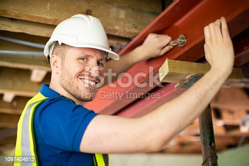 Construction Worker Fitting Steel Support Beam Into Renovated House Ceiling
