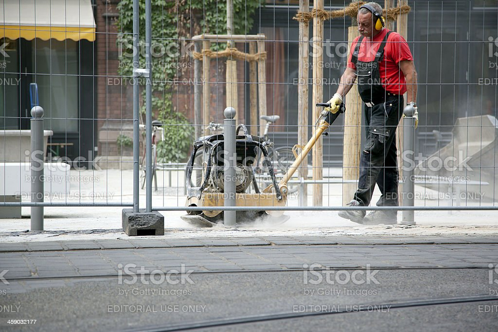 Construction worker flooring a sidewalk royalty-free stock photo