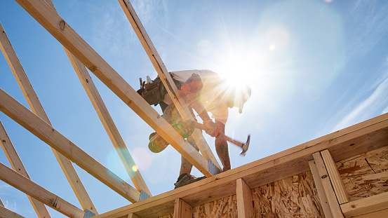 Construction worker framing a building against a sunny blue sky.