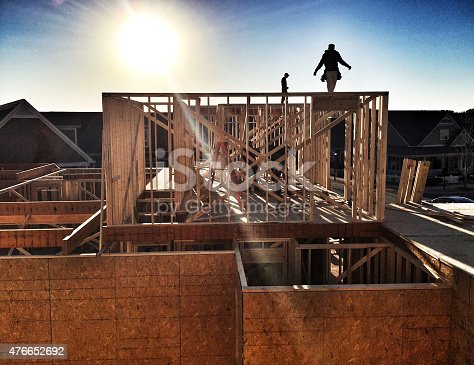 Construction worker framing a house using a air compressor and air gun.