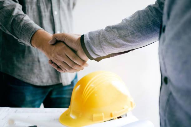 bauarbeiter gruß einen vorarbeiter bei renovierung der wohnung. - legere arbeitskleidung stock-fotos und bilder