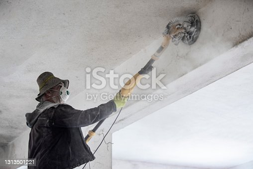 Construction worker working with Grinding Machine, dust appears due to grinding