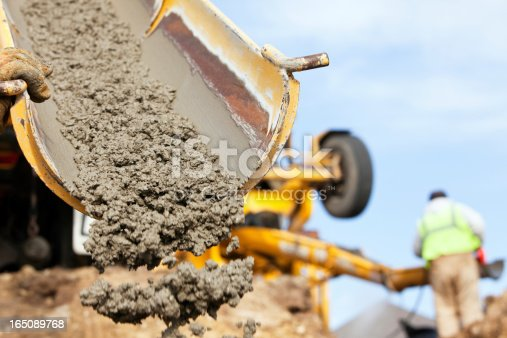 A construction worker is guiding a cement mixer truck chute as concrete is being offloaded for a new house footing. The background is overcast blue sky with another worker, wearing a safety vest, cleaning a mixer chute.http://www.banksphotos.com/LightboxBanners/Concrete.jpg