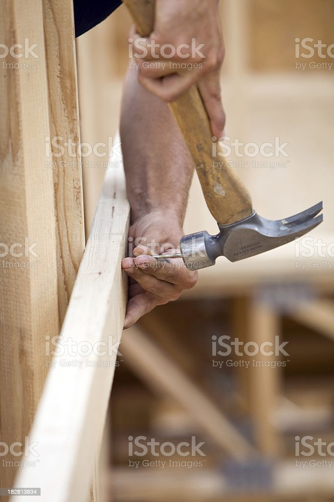 Construction Worker Hammering a Framing Nail from Above stock photo