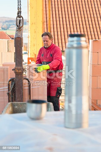 istock Construction worker handling bricks on a cold autumn day 681983694