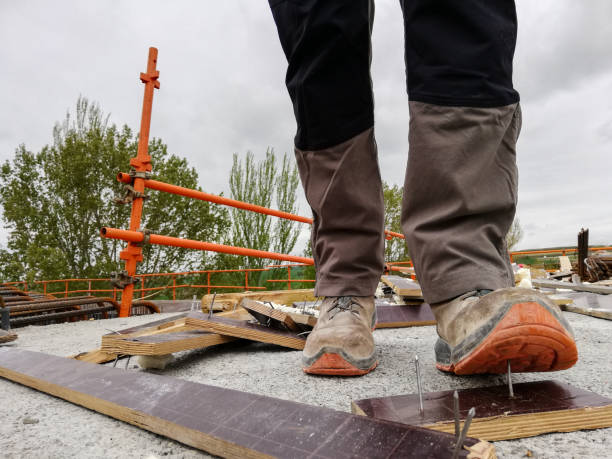 A construction worker has an accident while walks through a site with debris and stepping on a nail stock photo