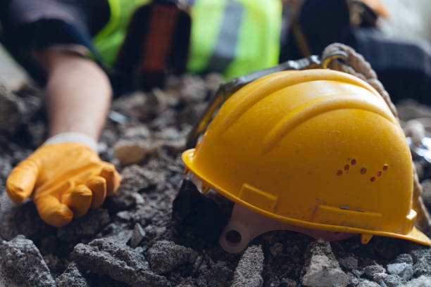 Construction worker has an accident while working on new house. Construction worker lies on the floor at the work site. Work accident stock photo