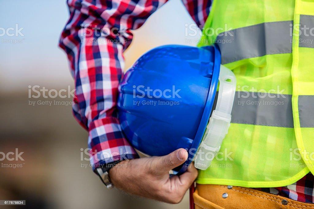 Construction worker holding a blue helmet stock photo