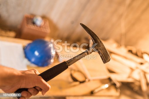936384788 istock photo Construction worker holding a hammer. 1074308930