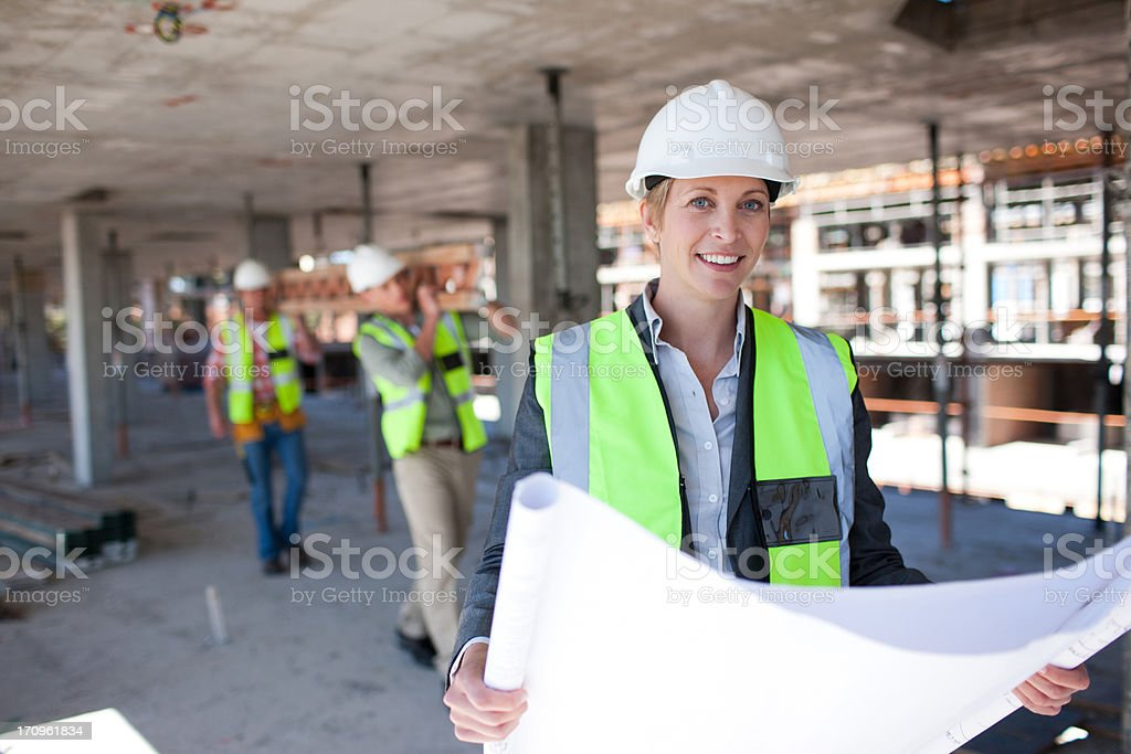 Construction worker holding blueprints on construction site royalty-free stock photo