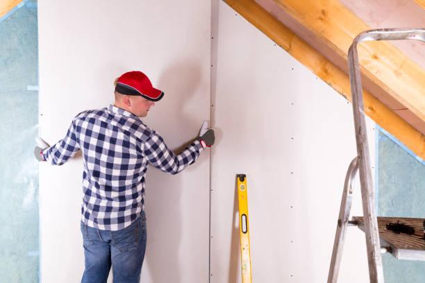 Panneau de gypse de tenue de travailleur de construction. Rénovation grenier. Installation de cloisons sèches - Photo