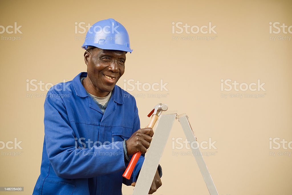 Construction worker holding hammer on ladder royalty-free stock photo