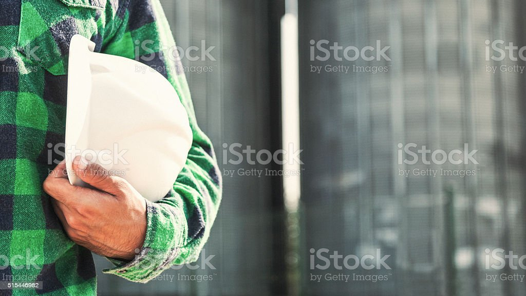 Construction worker holding hardhat stock photo