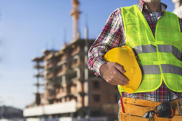 Construction Worker  holding helmet stock photo