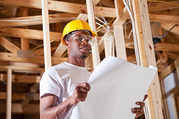 Construction worker holding plans stock photo