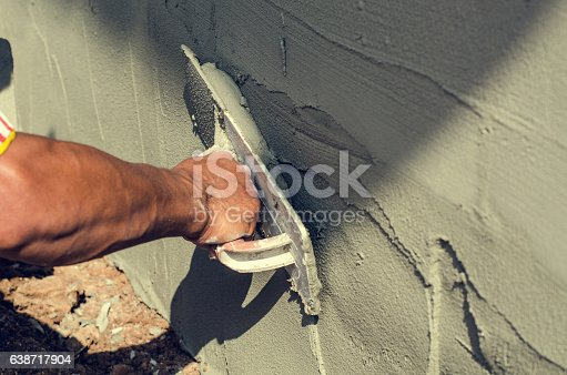 istock Construction worker holding plastering trowel smoothing wall defects 638717904