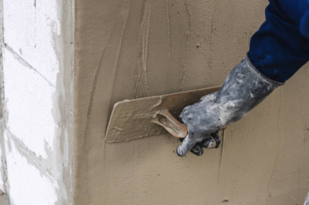 construction worker holding plastering trowel smoothing wall defects - pflasterbau stock-fotos und bilder