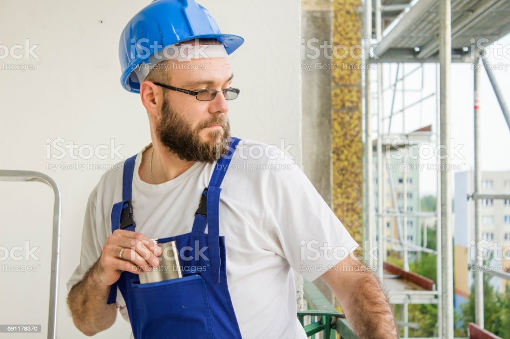 A construction worker in a work outfit, protective gloves and a helmet on his head pulls a silver hip-flask his pocket, looking back. Work at high altitude. Scaffolding in the background. stock photo