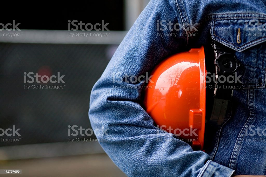 Construction worker in blue jean jacket with orange hard hat stock photo