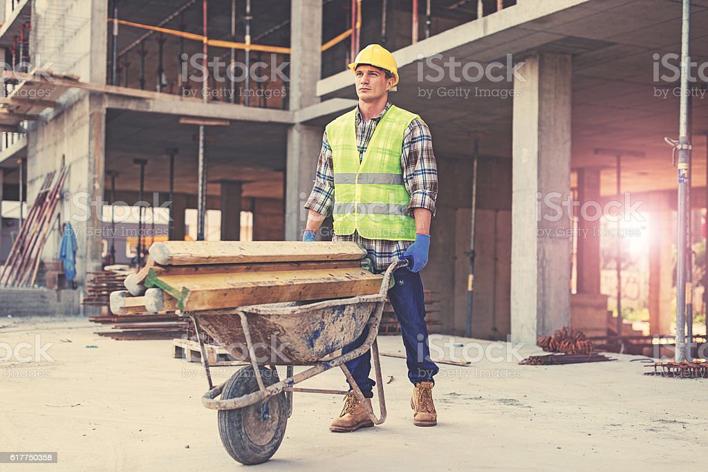 Construction worker in reflective clothing pushing wheelbarrow stock photo