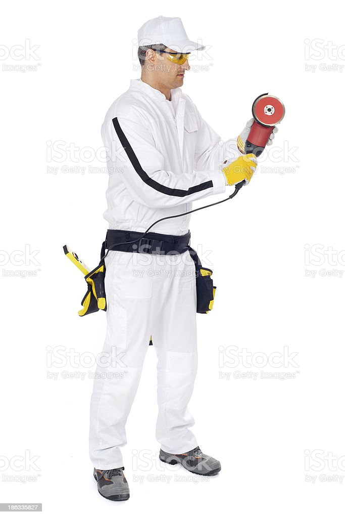 Construction worker in white overalls cuts with angle Grinder royalty-free stock photo