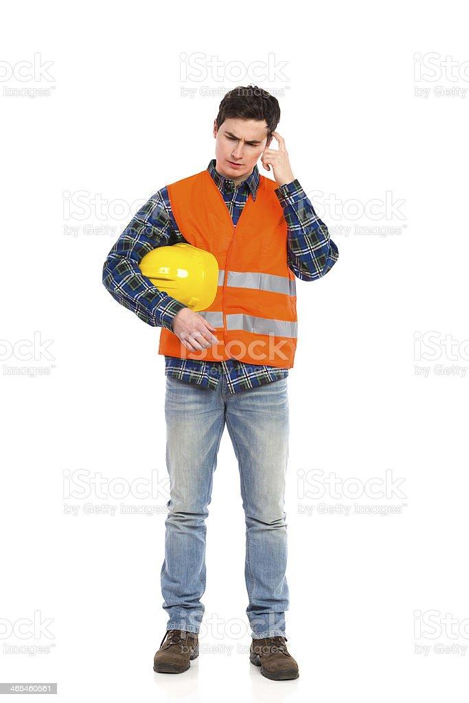 Construction worker in yellow helmet and orange waistcoat scratching head. stock photo