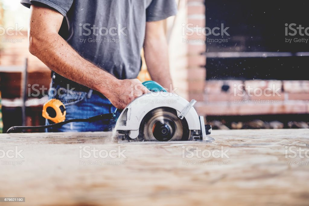 Construction worker, industrial carpenter using circular miter saw for cutting boards stock photo
