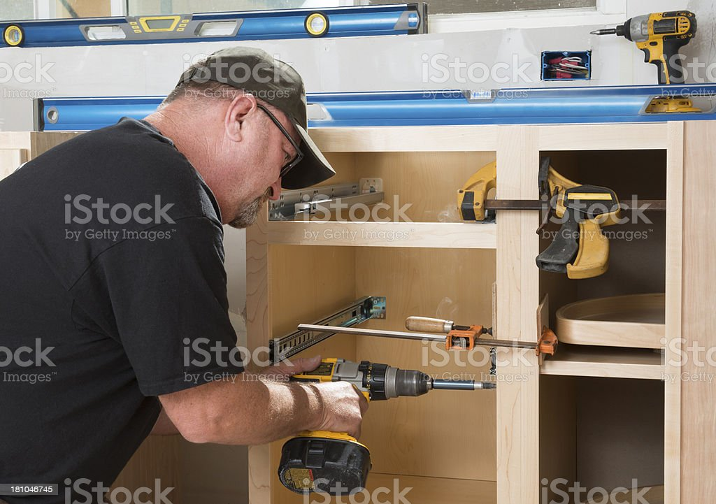 Construction Worker Installing Kitchen Cabinets royalty-free stock photo